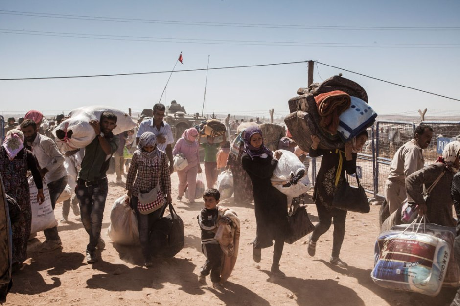 1/Syrian Kurdish refugees cross into Turkey from Syria, near the town of Kobani. The war that erupted in Syria in 2011 has propelled it into becoming the world's single largest driver of displacement.